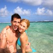 Stock Photo: Couple in a caribbean lagoon showing thumbs up