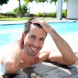Portrait of smiling guy in swimming pool — Stock Photo