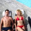 Fancy couple relaxing in longchairs by swimming pool — Stock Photo
