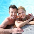 Cheerful couple relaxing in swimming pool — Stock Photo