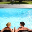 Back view of couple relaxing in swimming pool — Stock Photo