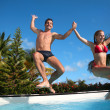 Young couple jumping in swimming pool — Stock Photo
