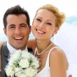 Cheerful married couple standing on the beach — Stock Photo