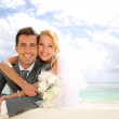 Just married couple leaning on fence by the beach — Stock Photo