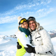 Cheerful couple standong on mountain peak — Stock Photo