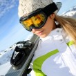 Portrait of woman at the mountain holding skis — Stockfoto