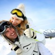 Skier at the mountain giving piggyback ride to girlfriend — Stockfoto