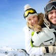 Cheerful snowboarder holding girlfriend on his back — Stock Photo #27923873