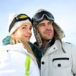 Portrait of couple of skiers looking at panorama — Stock Photo