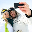 Skiers taking picture of themselves with smartphone — Stock Photo