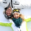 Cheerful couple laying down in snow — Stock Photo