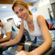 Woman exercising on bicycles in fitness gym — Stock Photo
