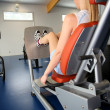 Stock Photo: Womexercising on legpress in gym center