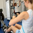 Woman using rowing equipment in gym center — Стоковая фотография