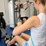kürek çekme ekipmanları gym center kullanan kadın — Stok fotoğraf