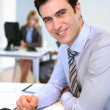 Portrait of smiling businessman in office — Stock Photo