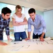Stock Photo: Team of architects working on construction plans