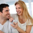 Cheerful woman showing smartphone to boyfriend — Foto Stock