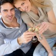 Cheerful couple celebrating with glass of sparkling wine — Stock Photo #27926143