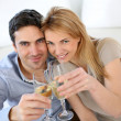 Cheerful couple celebrating with glass of sparkling wine — Stock Photo #27926151