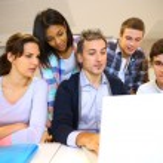 docente con estudiantes en la clase trabajando en portátil — Foto de Stock