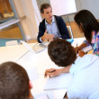 Teacher giving business presentation to students — Stock Photo #27927119