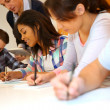 Group of teenagers in class writing an exam — Foto Stock