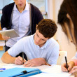 Teacher watching students writing exam — Stock Photo
