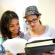 Teenagers in school hallway reading books — Stock Photo