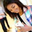 Cheerful student girl writing message on smartphone — ストック写真