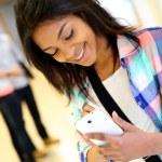 Веселые студенческие девушка, писать сообщения на смартфон — Стоковое фото