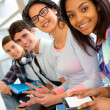 Group of cheerful teenagers sitting on school bench — Stock Photo