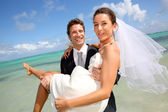 Groom holding his bride by the Caribbean sea — Stock Photo