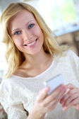 Smiling blond woman talking on cellphone with handsfree — Stock Photo