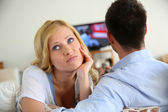 Blond woman being bored watching tv ith boyfriend — Stock Photo
