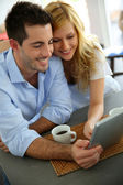 Young couple websurfing with tablet in home kitchen — Stock Photo