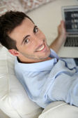 Upper view of young man using laptop computer at home — Foto de Stock