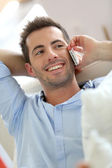 Relaxed young man talking on the phone in sofa — Stock Photo