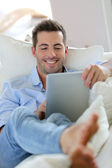 Cheerful young man laying in sofa with digital tablet — Stock Photo