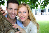 Cheerful young couple standing under tree — Stock Photo