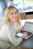 Cheerful blond girl connected on internet in home kitchen — Stock Photo