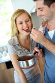 Woman tasting italian sauce cooked by boyfriend — Stock Photo