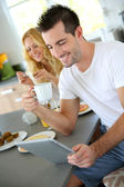 Young man sitting in home kitchen with tablet — Stock Photo