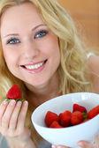 Attractive blong girl eating strawberries — ストック写真