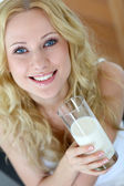 Beautiful woman holding glass of fresh milk — Stock Photo