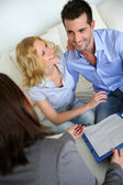 Cheerful couple signing property contract with real-estate agent — Foto Stock