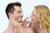 Woman applying sunscreen on her boyfriend's cheeks — Stock Photo