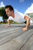 Young man doing pushups on pool deck — Stock Photo