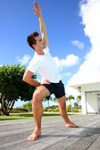 Young man doing stretching exercises by the pool — Stock Photo