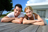 Young couple relaxing on pool deck after exercising — Stock Photo
